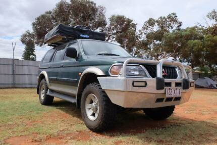 Mitsubishi Challenger with rooftop tent and camping equipment