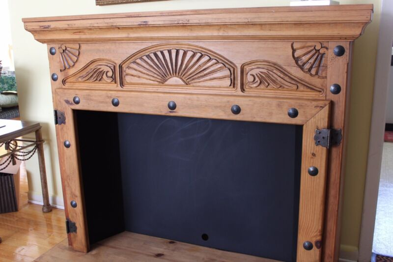 Wood Fireplace Mantel with Carved Design and Metal Decor