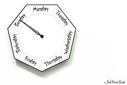 DayClocks - Hexagon White Wall Clock - Day of The Week Clock - Fun Clock Gift