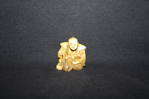 NETSUKE MAN SEATED WITH BOOK, BRUSH AND INK BLOCK