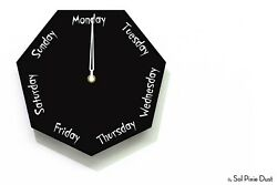 DayClocks - Hexagon Black Wall Clock - Day of The Week Clock - Fun Clock Gift