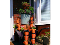 Large Terracotta + Ceramic Plant Pot Man in Flower Filled Metal Wheelbarrow