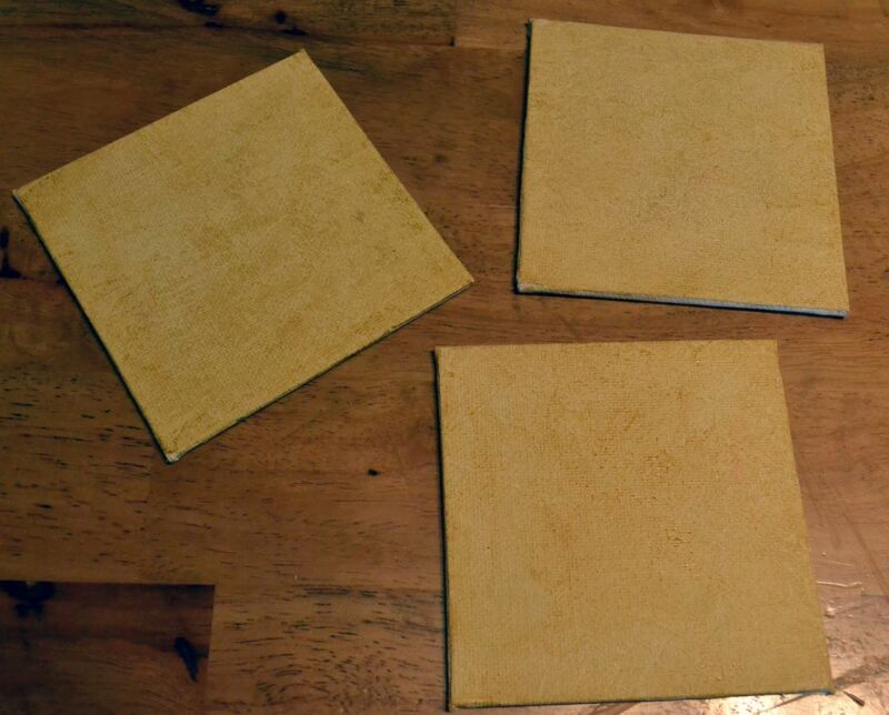 Three canvas boards being left to dry.