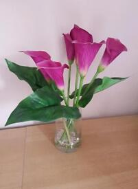 Artificial pink flowers and glass vase