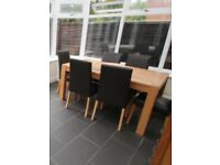 Solid oak dining table and 6 faux brown chairs