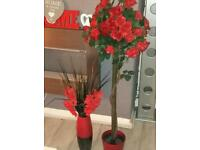 Artificial red roses in pot and large red vase