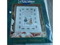 New counted cross stitch kit of a sampler. Picture is of children, cart, alphabet, flower border.