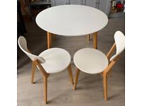 Round white top dining table and two matching chairs