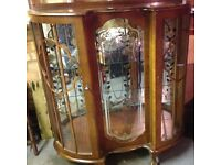 Bow fronted glass cabinet, with rose patened mirror back and two glass shelves