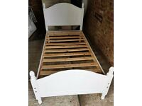 White wooden single bed with mattress