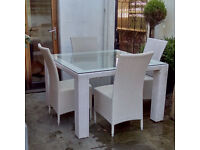 Four chairs and a glass table top white rattian garden set. Very unusual to find white contemporary.