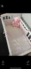 White Rocking crib with pink bedding and mattress.