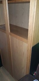 Tall Oak Ikea Billy bookcase with glass doors.