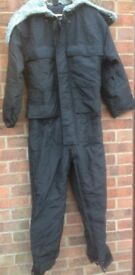 One piece lined, water resistant suit with hood.