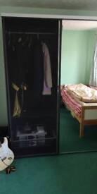 Empty IKEA black mirrored double wardrobe