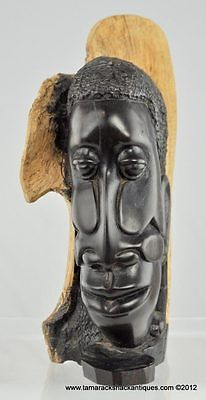 African Folk Art Carved Wood Statuette Long Faced Man Wooden Tree Background