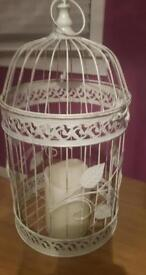 Large shabby chic bird cage with candle.