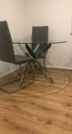 Round glass dining table with chrome legs