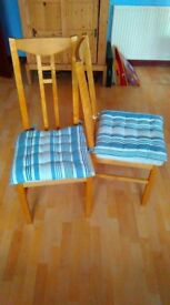 Two dining room chairs with cushions.