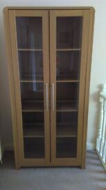 Tall bookcase or cabinet with glass doors, light oak effect veneer.