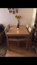 Wooden dining room table and cream chairs