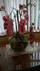 Atifical orchids in ceramic bowl