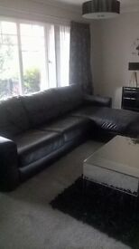 Black large sofa with chaise end, and pull out double bed, 1chair and stool
