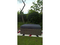 A New Large Rattan Garden Seating Bench with a Grey Fabric Material Cushioning.