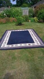 An attractive dark blue carpet with design around the border.