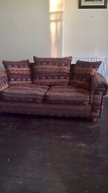 Sofa, multi coloured but mainly red. Good condition with reversable cushions