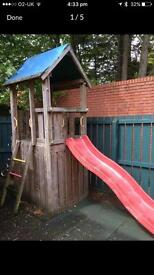 Jungle gym climbing frame with slide and play house.