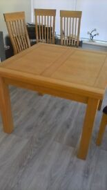 solid wooden dining table and six chairs. folding to sit 4 and exoads to sit 8.