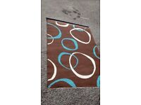 BROWN AND BLUE PATTERNED RUG MEASURES APPROX 115 CM X 164 CM.