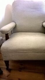 Lovely old armchair on castors with turned wooden front legs and upholstered arms, very comfy