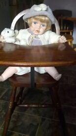 porcelain doll in a wooden vintage highchair