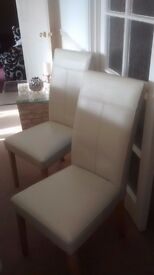 A pair of faux leather cream / ivory dining chairs.
