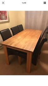 Solid oak wood dining table and six brown leather scroll top chairs.
