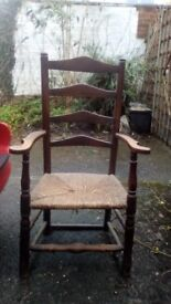 A generously proportioned antique rush seated, ladder back arm chair.