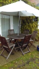 SOLID TEAK FURNITURE.. TABLE, SIX CHAIRS, UMBRELLA AND CAST IRON BASE