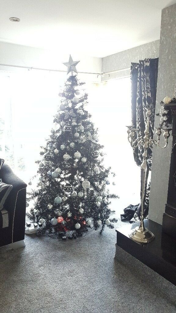7ft black christmas tree with silver and chrome decorations and fireplace garland
