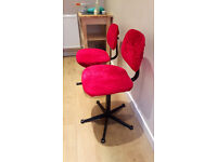 Two swivel (computer) chairs with red velvet covers grey/black underneath.