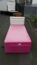 Single bed in pink with cream leather headboard also has storage