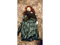 Porcelain doll wearing dark green dress & carrying an umbrella