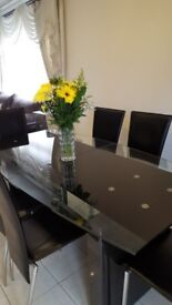 Stunning black and glass extendable dining table with 6 chairs