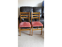 pair of wooden chairs with padded seat