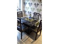 Glass Dining Table With Brown Stand In The Middle 4 Wooden Chairs Grey