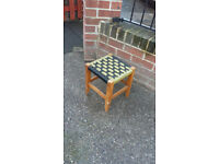 small wood framed stool with woven pattern seat