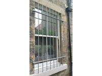 Two galvanised steel security window grills