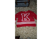 Red baggy fit jumper with white K print on the front.