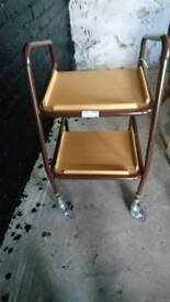 Patterson Medical Teak Shelf Trolley Adjustable Height used to assist elderly person carrying Food
